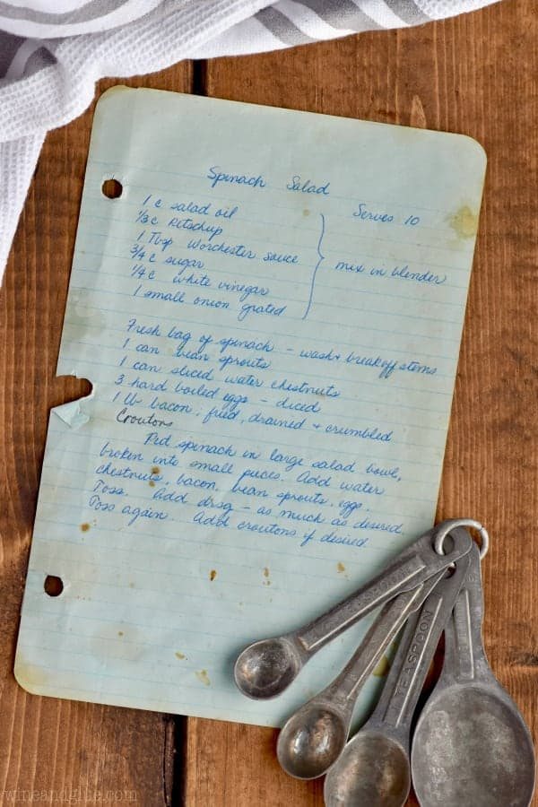 An overhead photo of a piece of paper with a spinach salad recipe and measuring spoons.