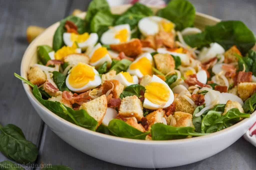 white bowl filled with spinach salad with bacon, hard boiled eggs, and croutons on a blue wood board