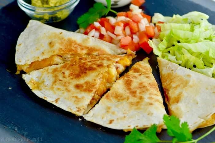 Cut into small triangles, the Taco Bell Chicken Quesadilla has a side of guac and pico de gallo.