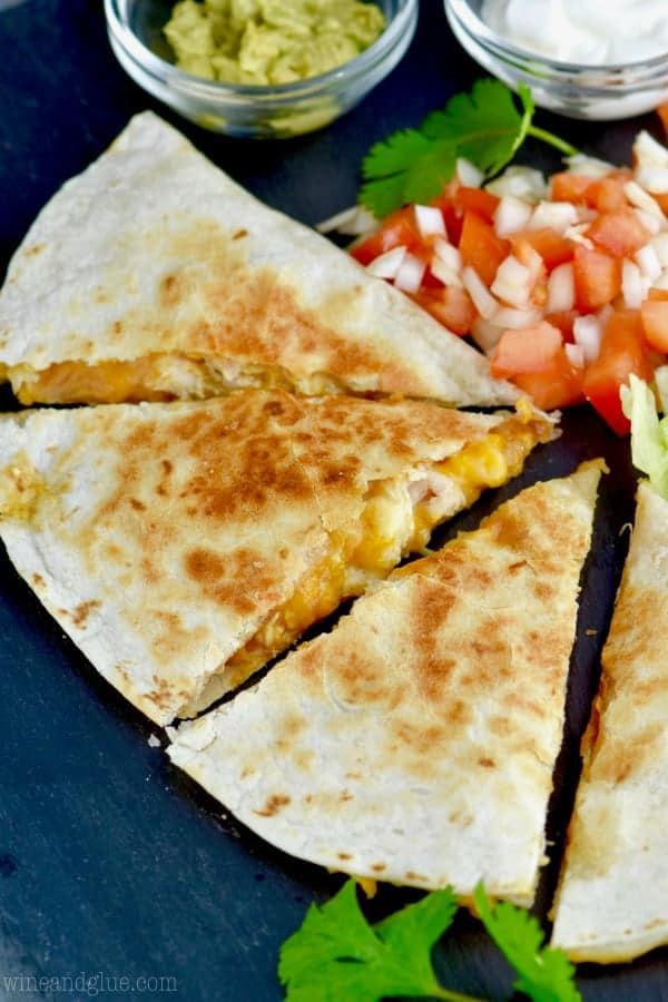Cut into triangles, the Taco Bell Chicken Quesadilla has a side of guac, pico de gallo, and sour cream.