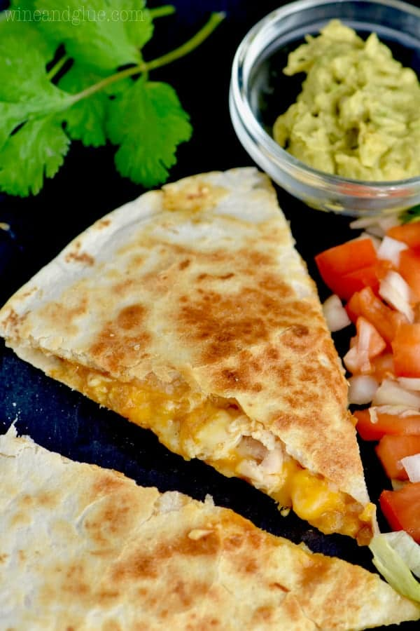 A close up photo of the Taco Bell Chicken Quesadilla with a side of guac and pico de gallo.