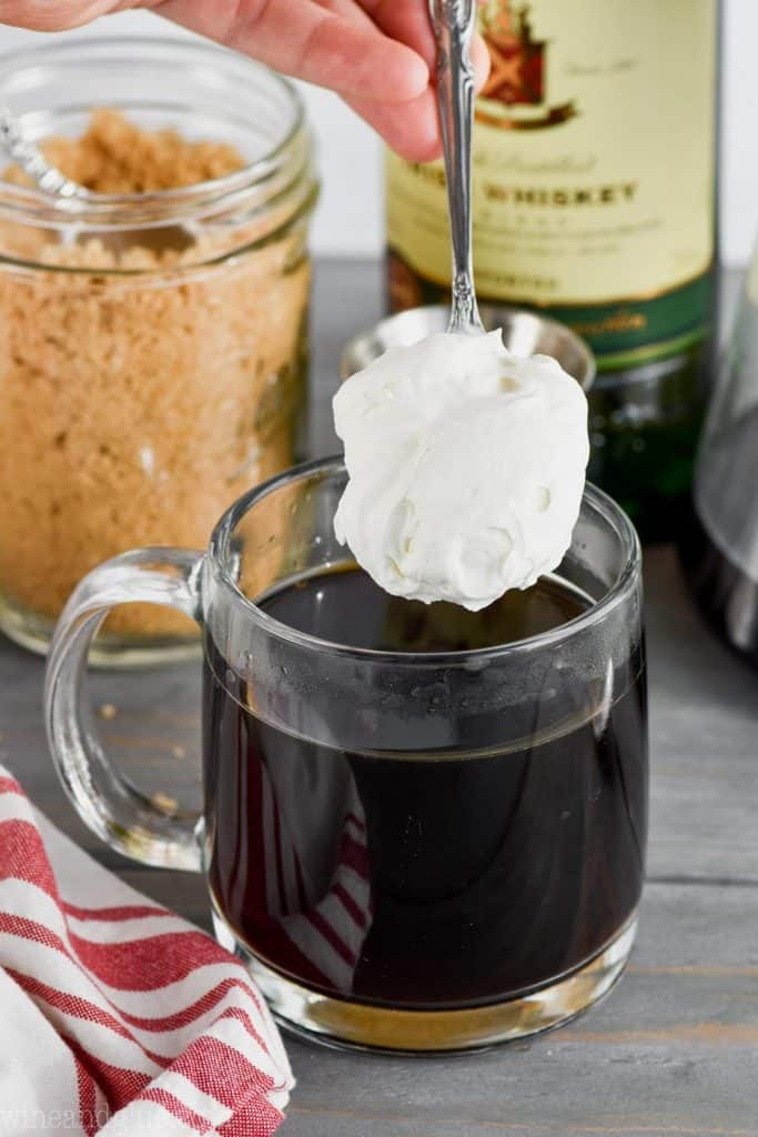 whipped cream being added to the top of irish coffee