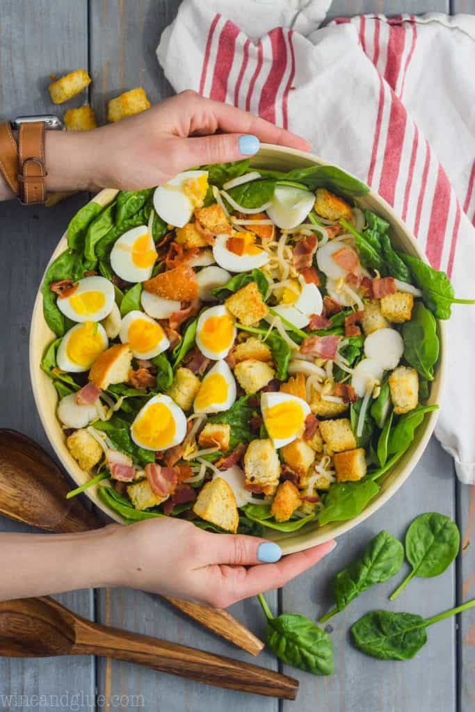 two hands holding a white salad bowl filled with the best spinach salad topped with sliced boiled eggs, bacon, and cheese.