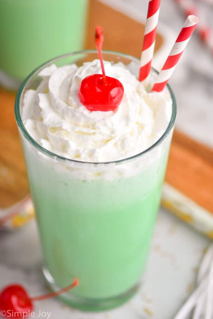 close up overhead of a tumbler filled with McDonald's shamrock shake, topped with whipped cream and a cherry