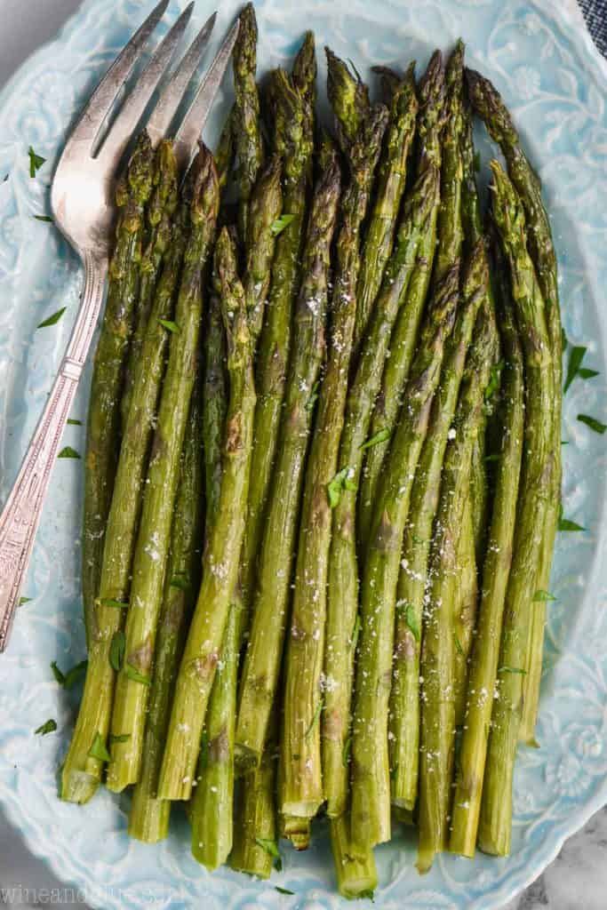 blue oval plate with oven roasted asparagus and vintage serving fork underneath