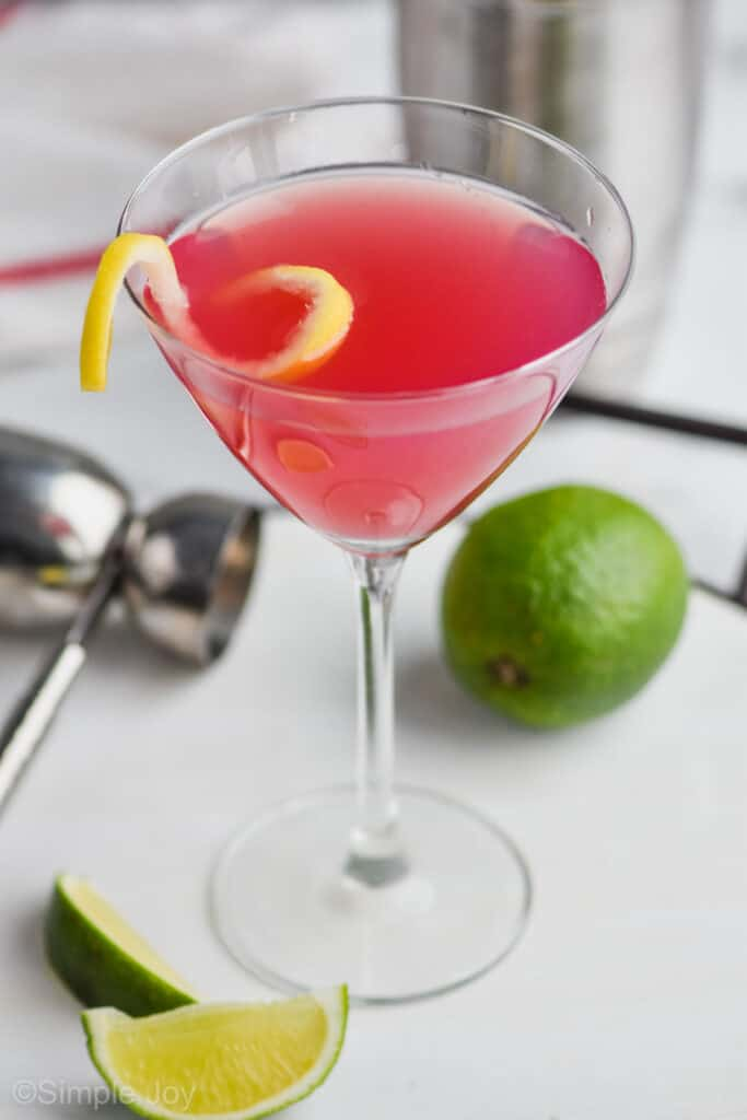 overhead view of a martini glass filled with pink cosmopolitan drink recipe with a lemon curl on a white tray with a silver jigger and a lime next to it
