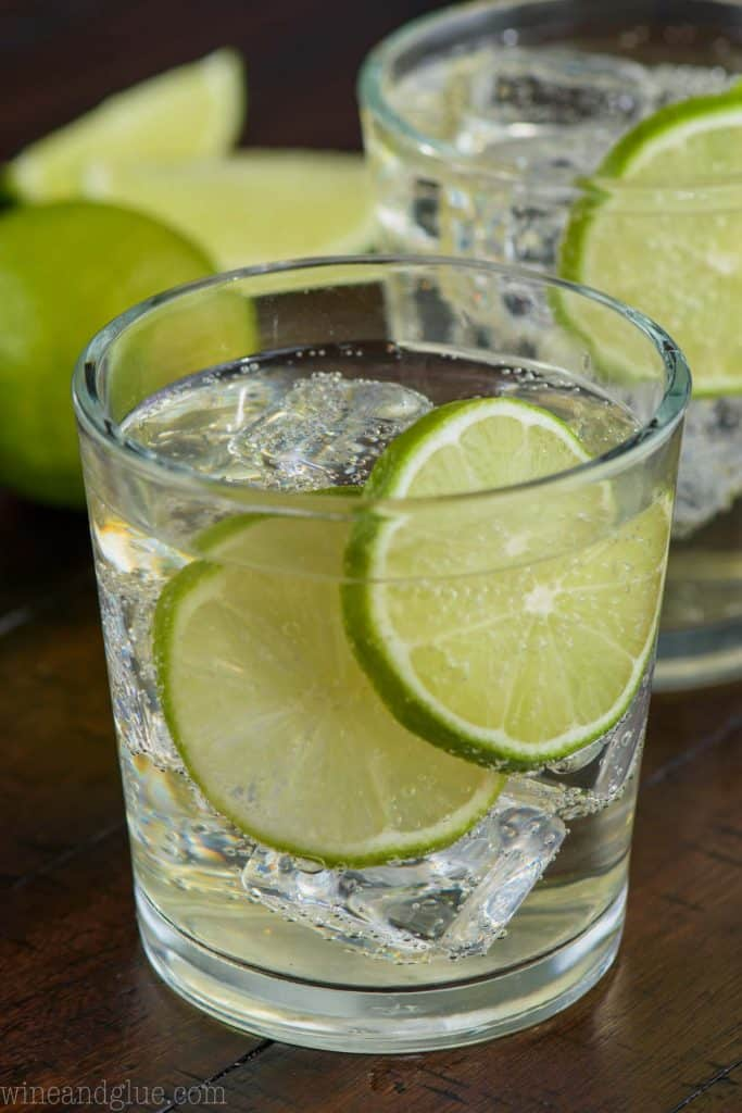 up close view of a gin and tonic recipe in a small tumbler with two lime slices and ice and another glass in the background