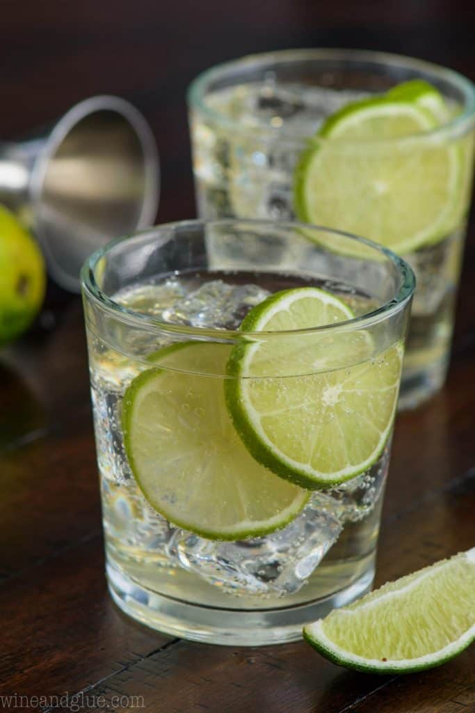 two glasses of gin and tonic, each garnished with lime slices and full of ice