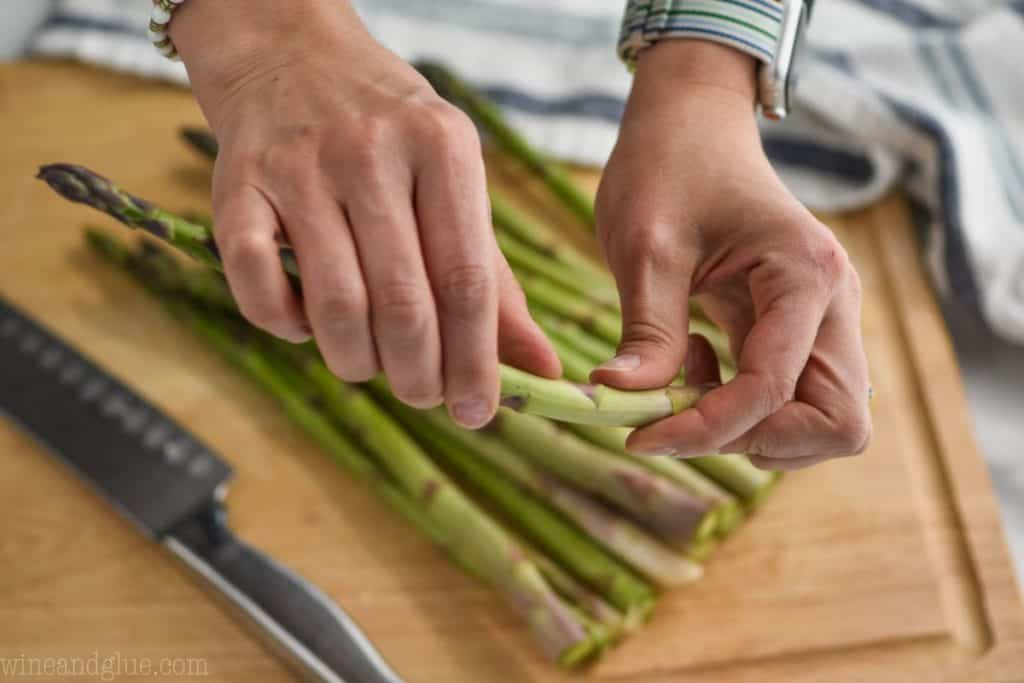 woman holding asparagus and snapping the bottom part of the stem off