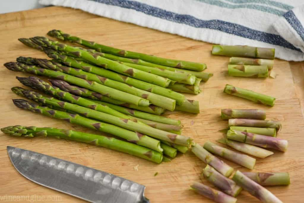 bunch of asparagus on a wood cutting board with woody bottoms snapped off to make oven roasted asparagus