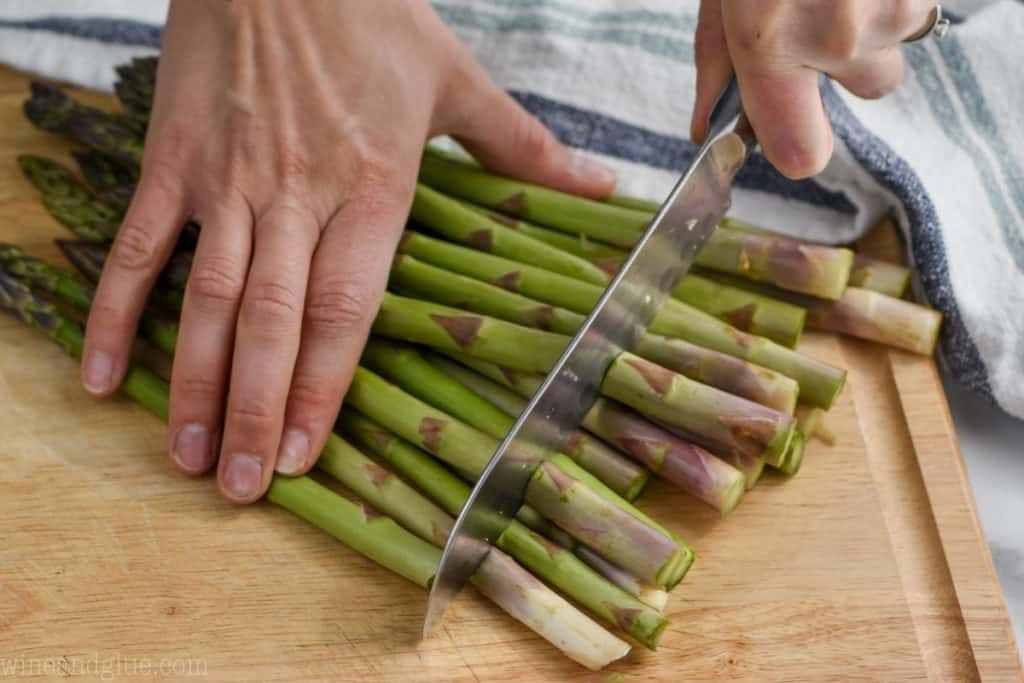woman using a knife to cut off the woody bottoms of asparagus