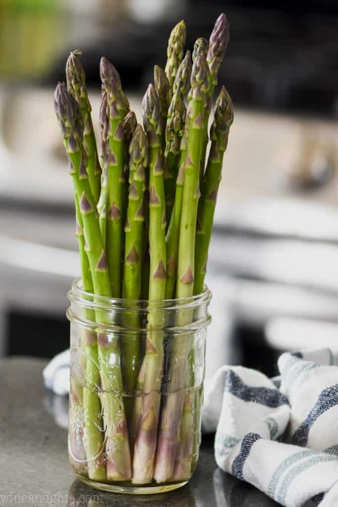 bunch of asparagus in a mason jar with a little water to store in the refrigerator