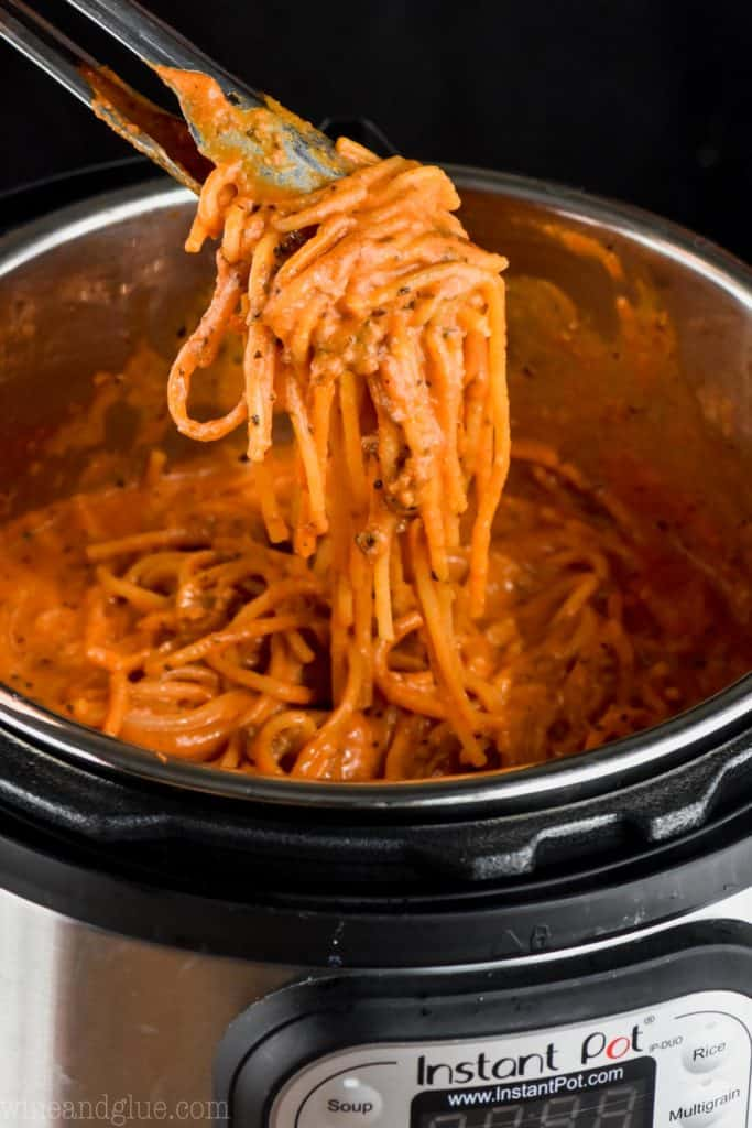 tongs holding delicious creamy instant pot spaghetti over an instant pot