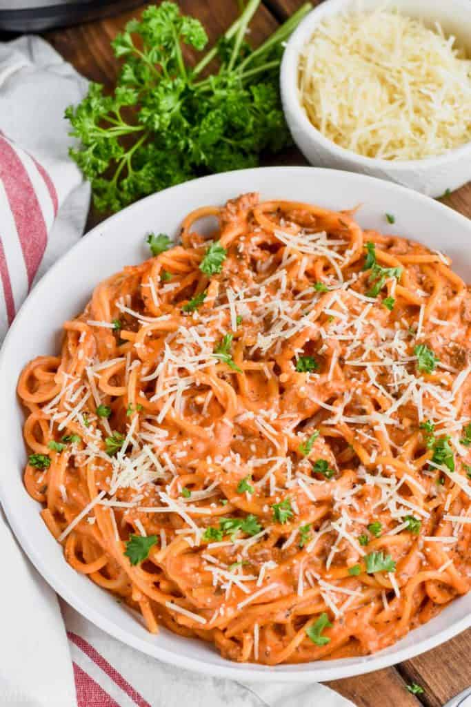 bowl of creamy instant pot spaghetti with shredded parmesan and parsley
