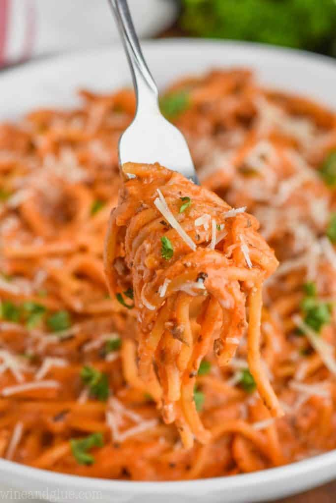 forkful of creamy instant pot spaghetti that is garnished with parsley and shredded parmesan