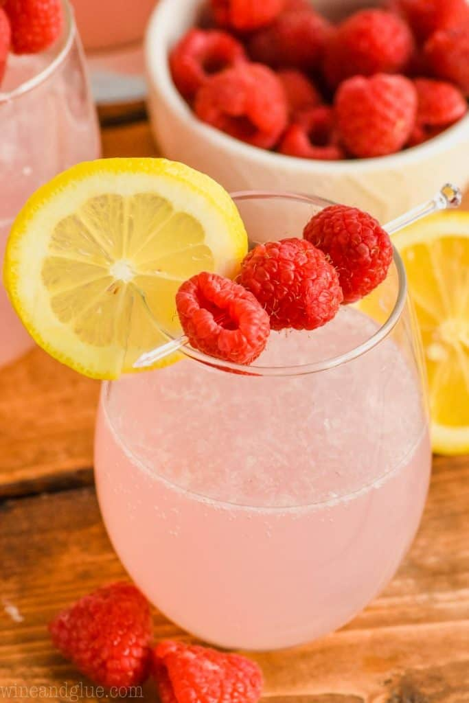 stemless wine glass full of pink lemonade vodka punch garnished with a lemon slice and some fresh raspberries