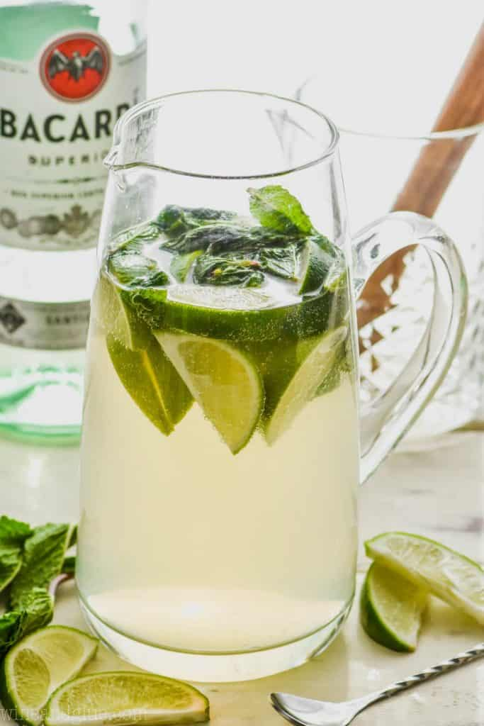 pitcher of mojito sangria recipe with limes and mint and a bottle of bacardi in the background