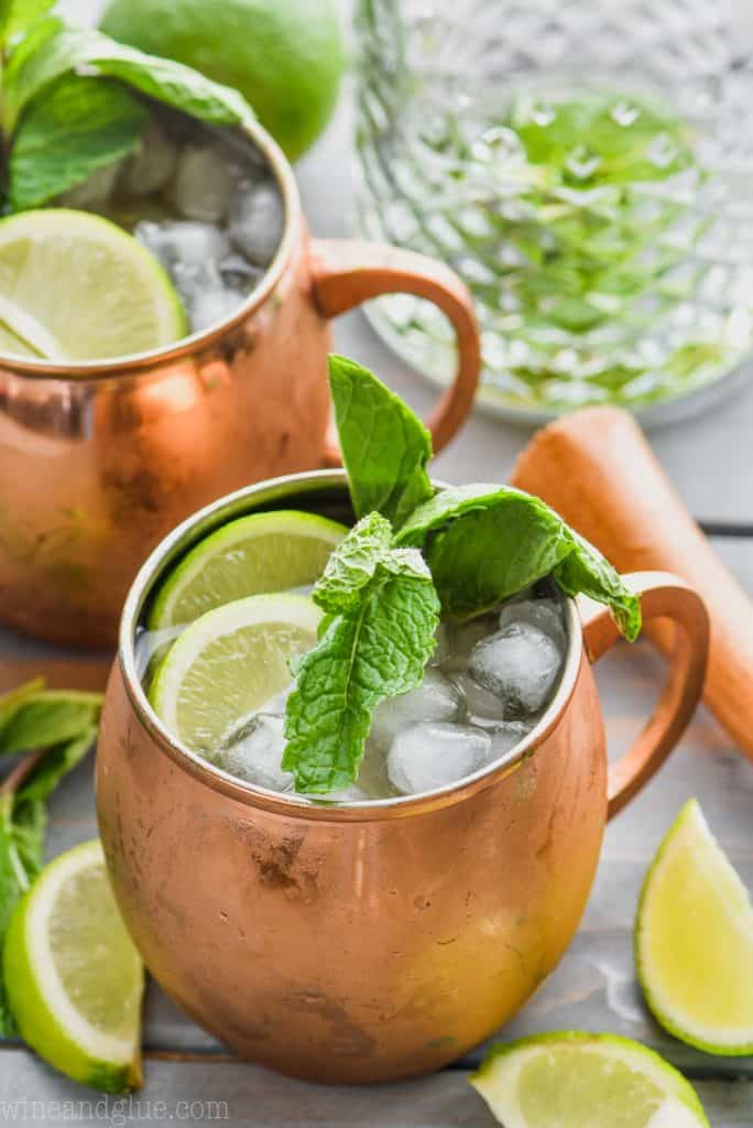 moscow mule with gin in copper mug garnished with mint and lime next to another moscow mule with gin and a mixing glasss