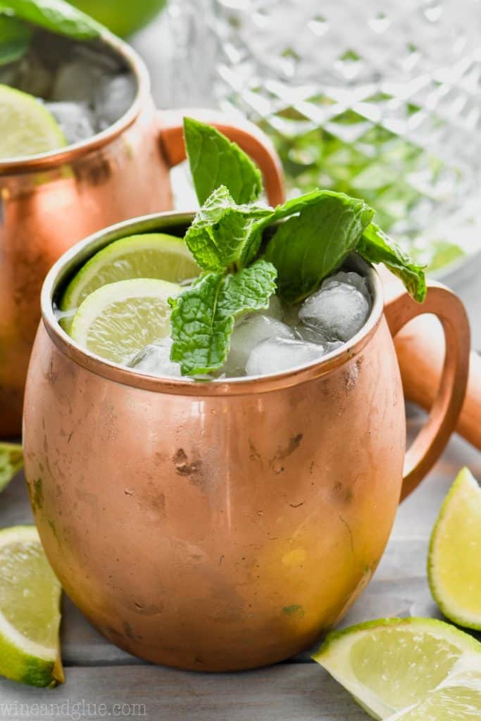 moscow mule with gin in copper mug garnished with mint and lime, a mixing glass in the background