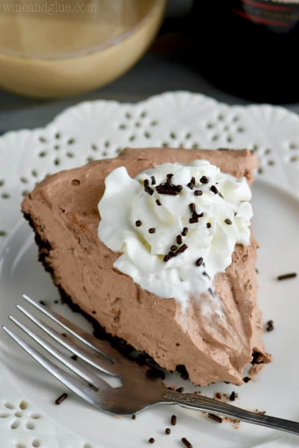 With a small bite, a slice of No Bake Baileys Chocolate Pie has a small dollop of whip cream and chocolate sprinkles.