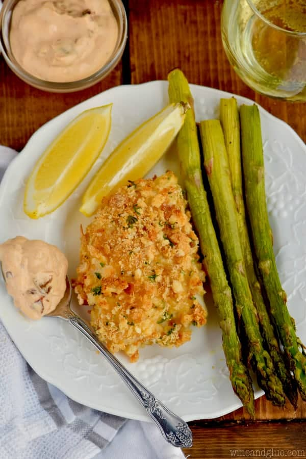 fish, asparagus, lemons, and chipotle horseradish sauce on a white plate