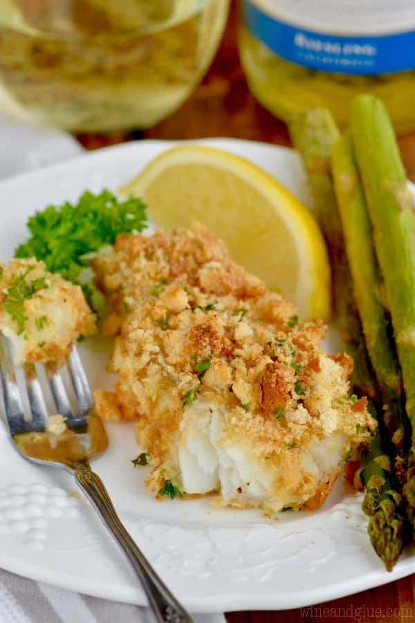 baked fish that is breaded with a side of asparagus and a slice of lemon