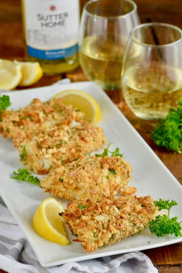 five pieces of oven fried fish on a platter with a slice of lemon and a glass of white wine