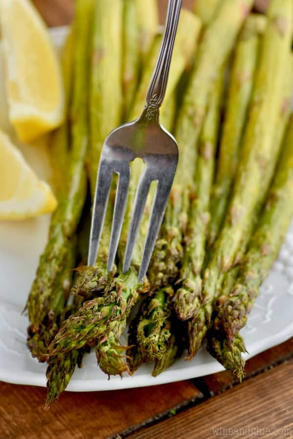 fork spearing asparagus on a plate
