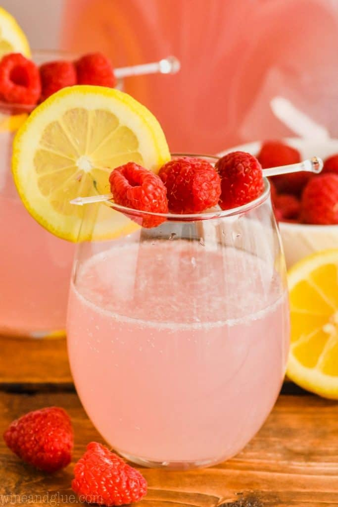 stemlesss wine glass with a lemon slice and three raspberries skewered over a pink lemonade vodka punch