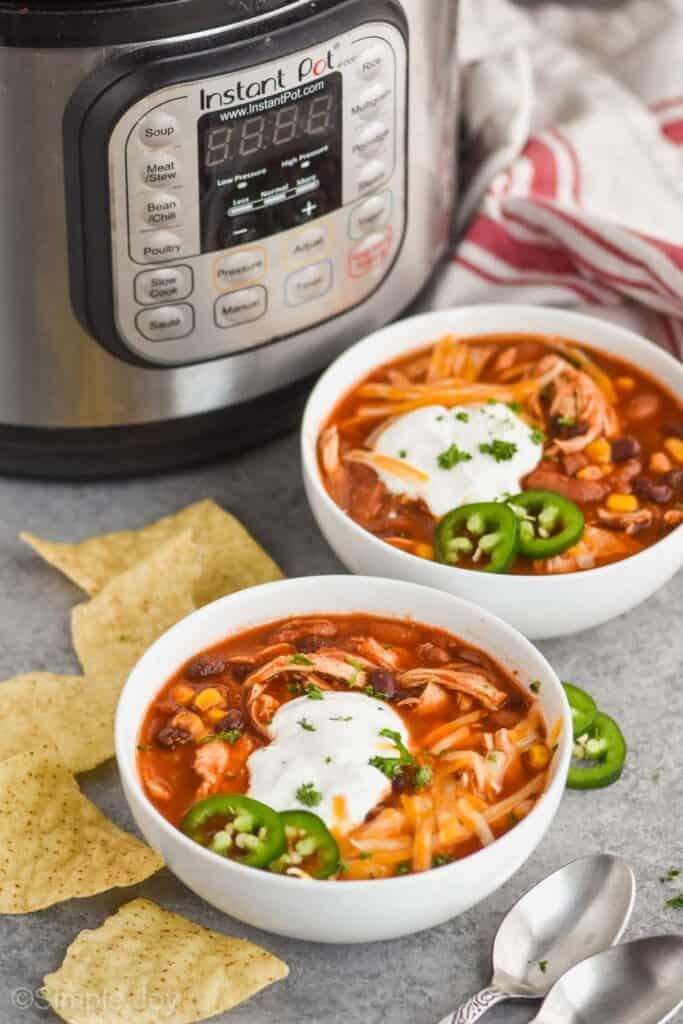 two white bowls full of chicken taco soup topped with sour cream and cheese  with tortilla chips around them and an instant pot int he background