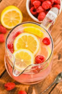 overhead view of a pitcher of pink lemonade vodka punch floating with fresh lemons and fresh raspberries