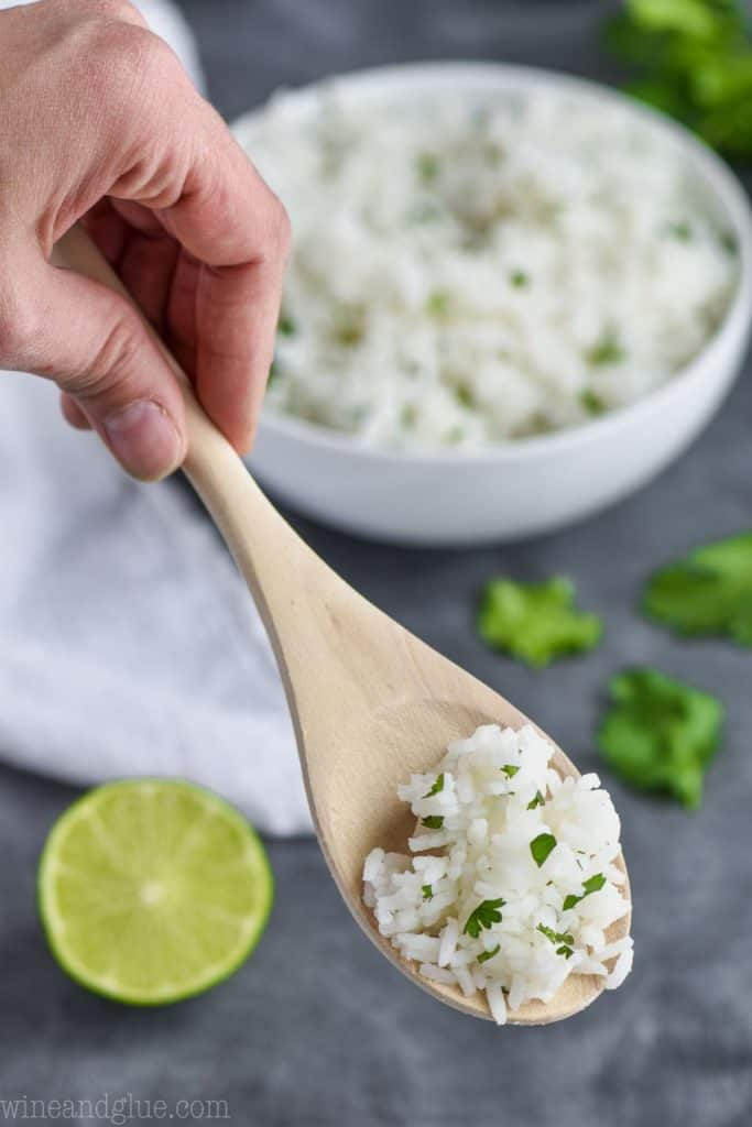 spoonful of rice with lime and cilantro with bowl in the background
