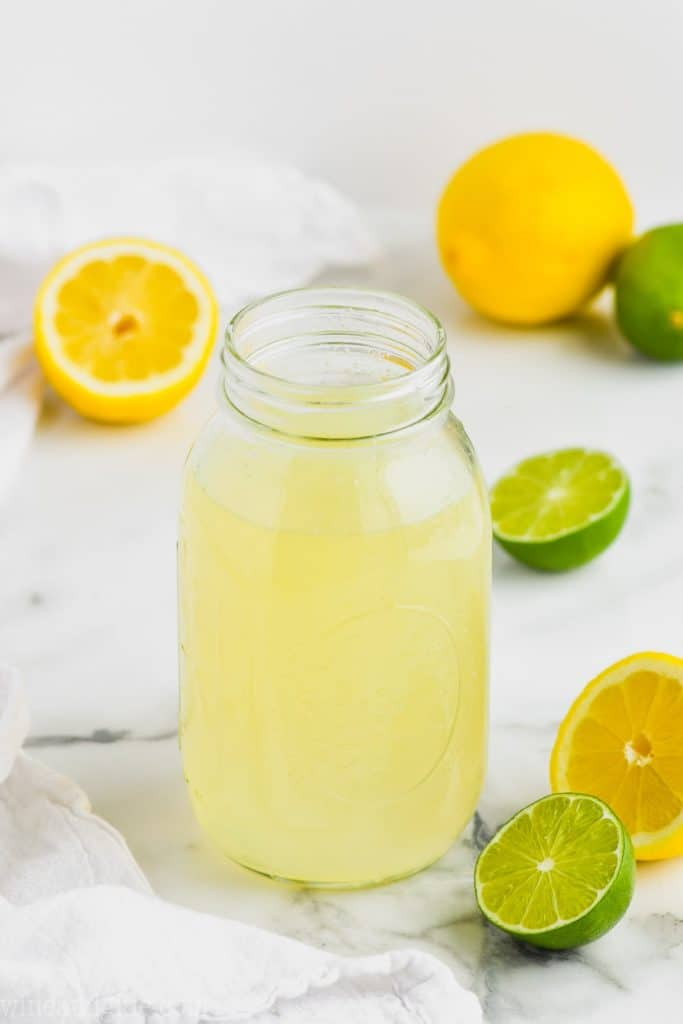 clear mason jar full of homemade sweet and sour mix with limes and lemons around it on marble counter top
