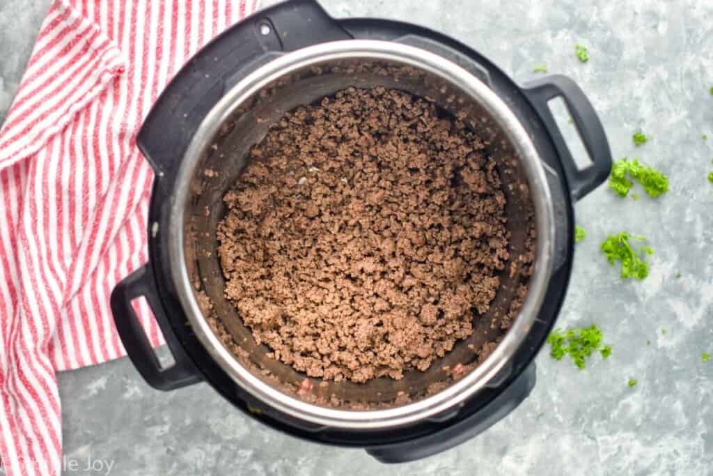 ground beef cooked in the bottom of an instant pot