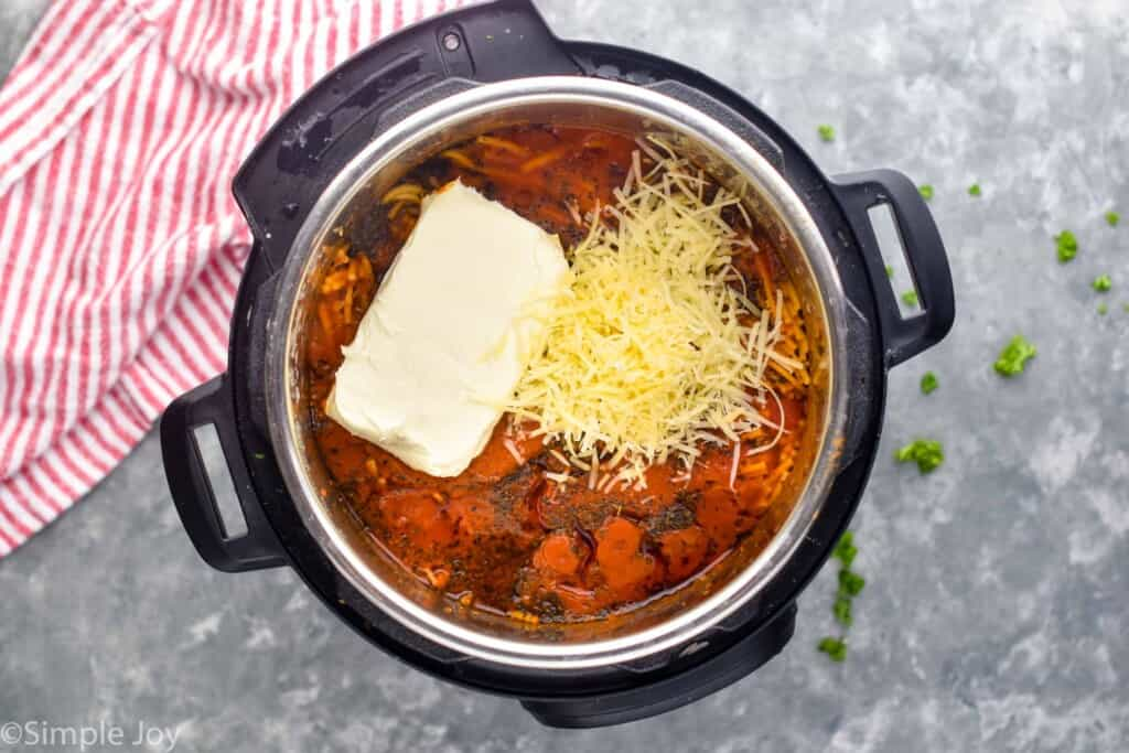 overhead of an instant pot filled with spaghetti sauce, a brick fo cream cheese, and Parmesan cheese