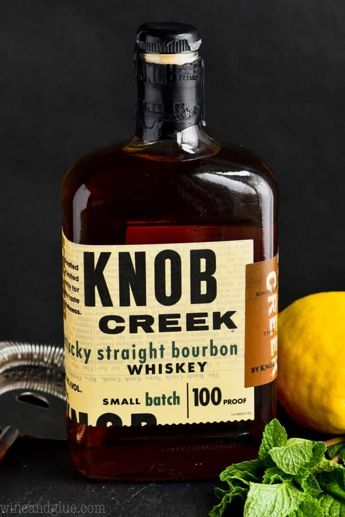 a bottle of knob creek whiskey surrounded by a cocktail strainer, fresh mint, and a lemon