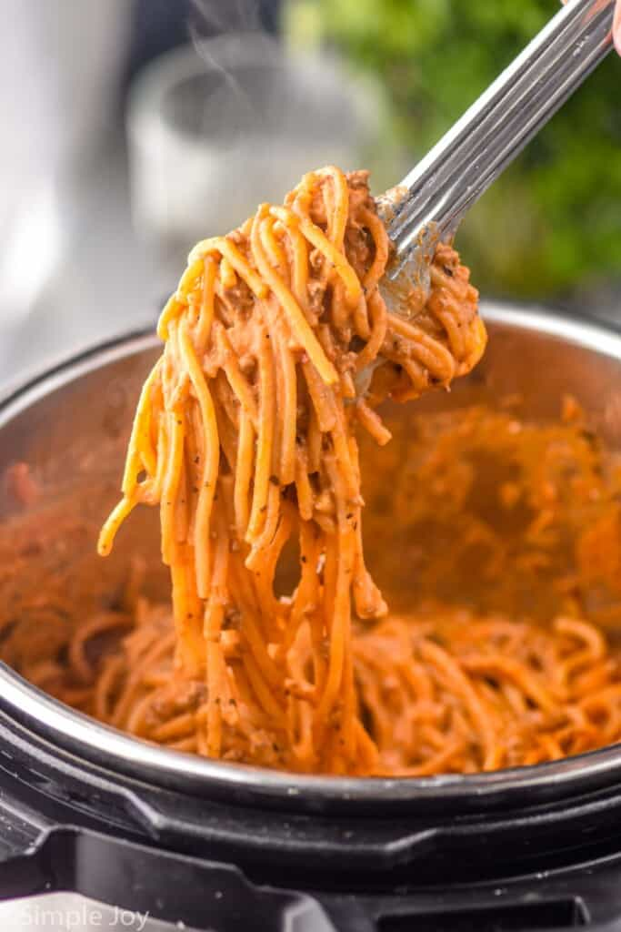 tongs lifting creamy spaghetti out of an instant pot