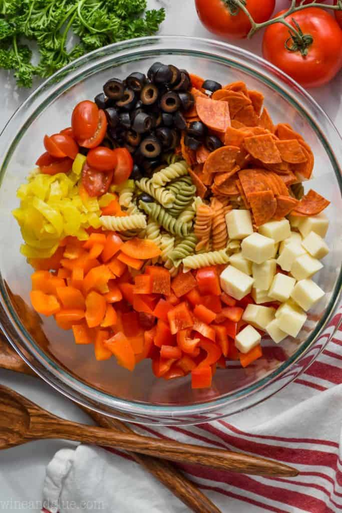 overhead photo of Italian pasta salad with peppers, cheese, pepperoni, olives, and tomatoes