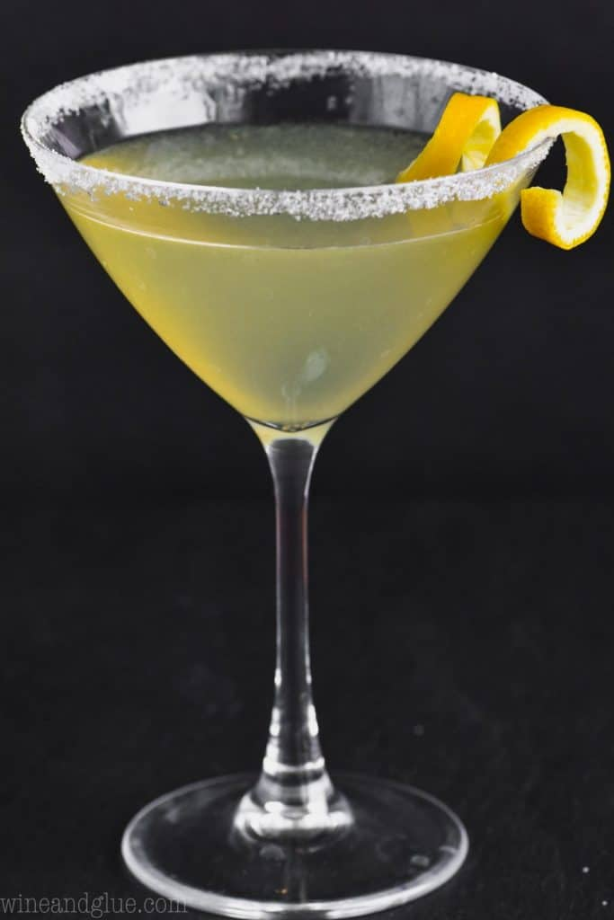 martini glass on a black background rimmed with sugar, full of a lemon drop martini and garnished with a lemon curl