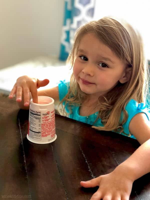 little girl eating yogurt with her fingers