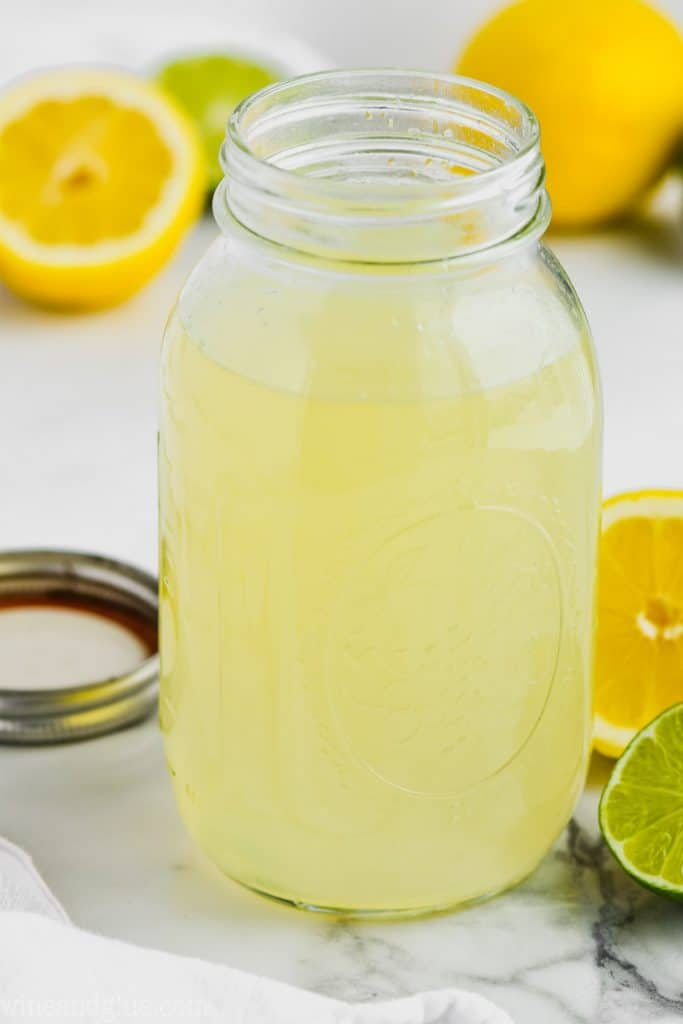 clear mason jar full of sweet and sour mix with limes and lemons around it on marble counter top