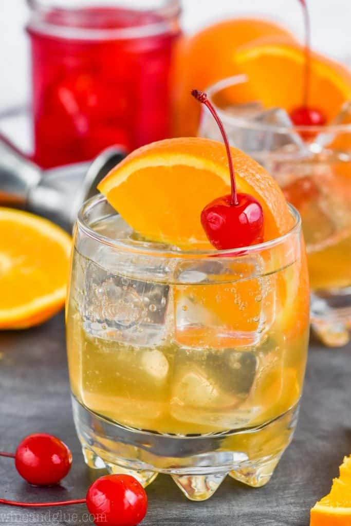 an amaretto sour drink in a glass with cherry and orange