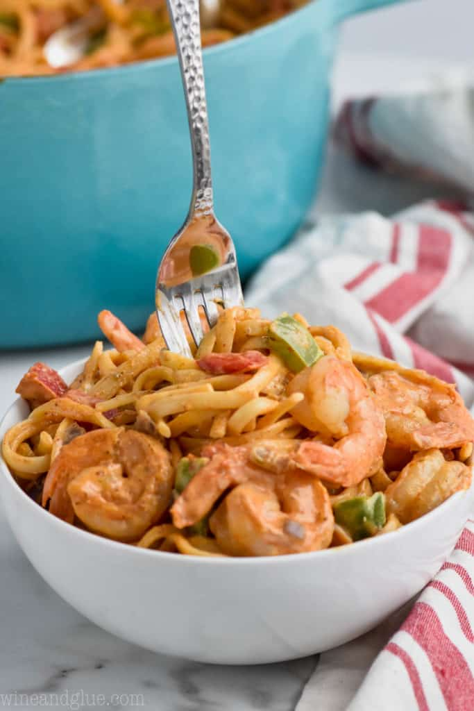 for in a bowl of tasty one pot shrimp fajita pasta with a fork coming out