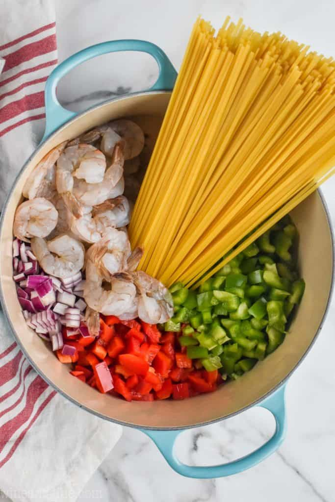overhead view of one pot pasta with peppers, onions, shrimp, and noodles