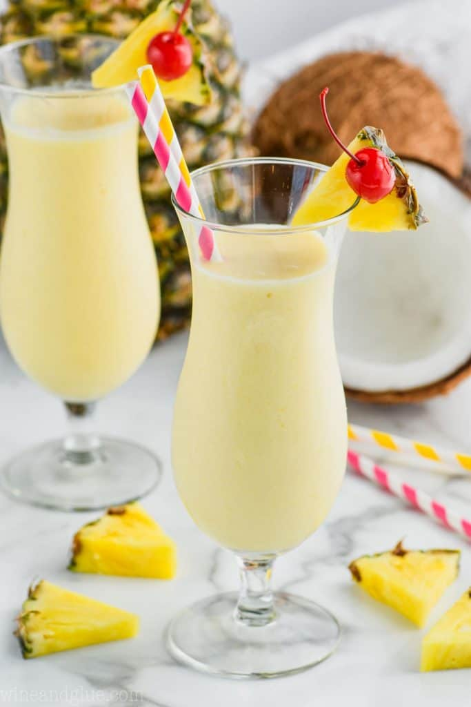 hurricane glass filled with an easy pina colada garnished with a pineapple