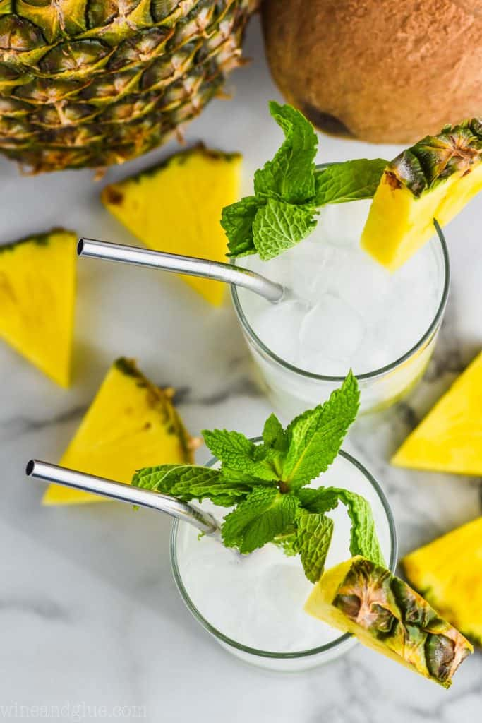 overhead view of two pineapple mojitos garnished with fresh mint, pineapple wedges, and pineapple wedges laying next to it
