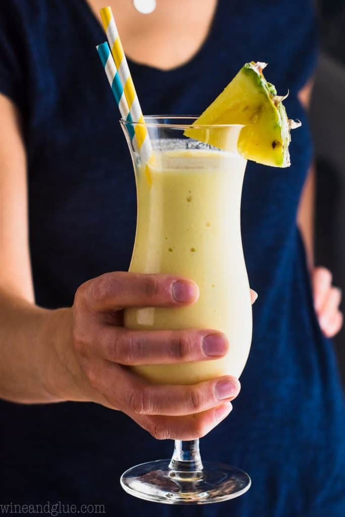 woman holding pina colada with coconut milk