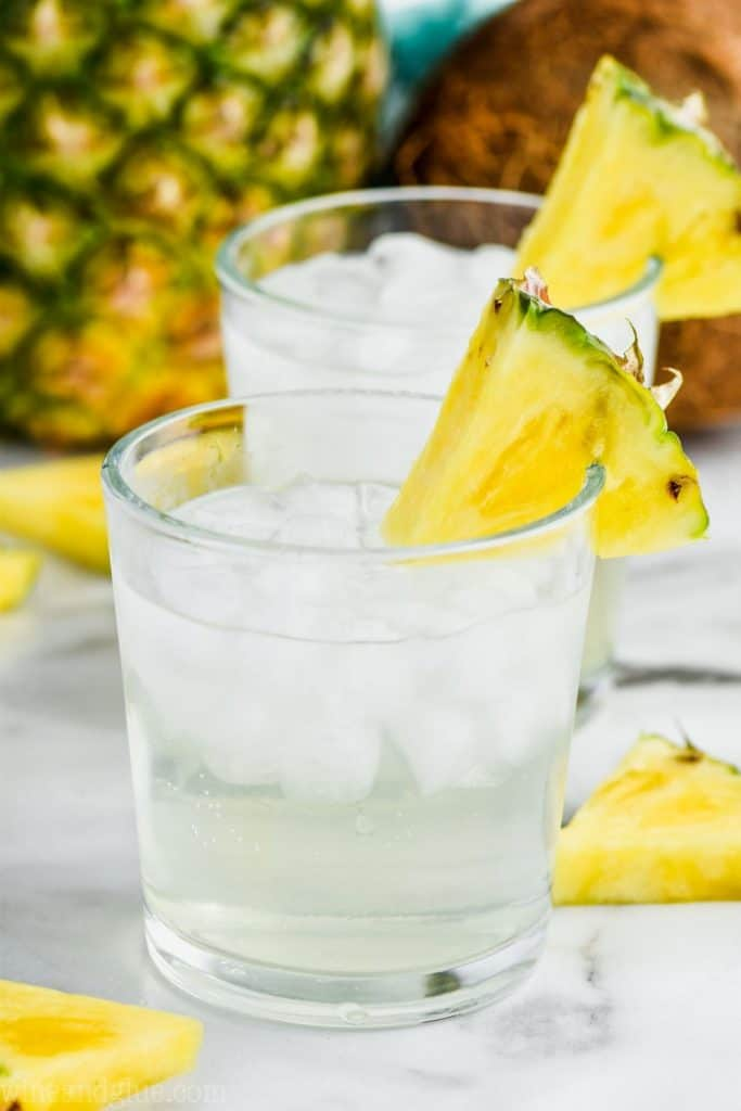 a tumbler full of ice and pina colada vodka soda, garnished with a pineapple wedge