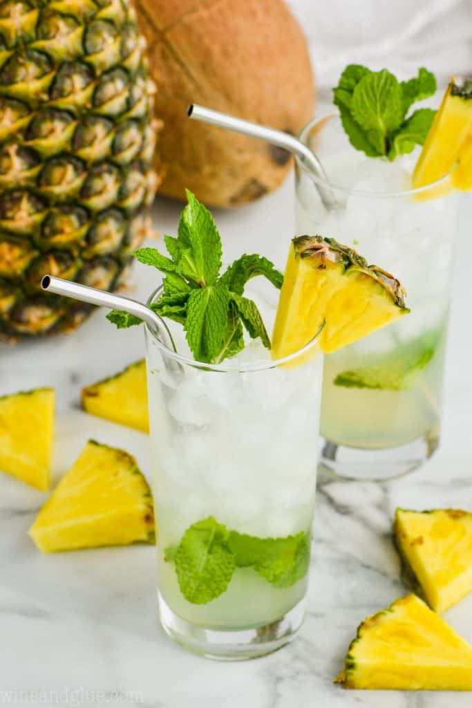 two high ball glasses filled with pineapple mojitos, garnished with pineapple wedges, and fresh mint with a pineapple and a coconut in the background
