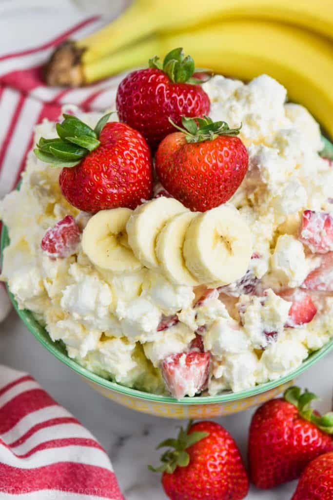 overhead view of strawberry banana fluff recipe in a bowl with fresh strawberries and bananas